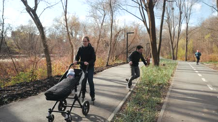 rolki : Young family walking in autumn with a baby in a stroller on roller skates in a sunny city park. Dad drives onto another track and overtakes mom. Slow motion.