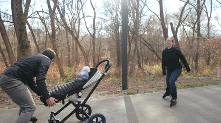 rolki : Happy parents with a stroller and roller skates in the cozy city park. Father roller skates backwards. Mother pushes the stroller forward, and dad catches her. Slow motion. Wideo