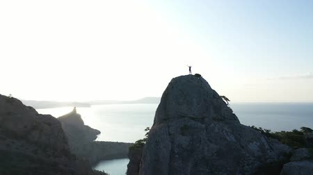 emelt : Aerial drone view, young woman just reached the mountain top. Adventure Woman with arms raised on mountain top looking at Sunset view over sea enjoying scenic nature landscape. Hiker Girl Vacation. Stock mozgókép