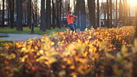 roller blading : A professional male roller blader performs cool tricks and dances on roller skates in a comfortable city park in the last days of autumn. Idea of outdoor activities and a healthy lifestyle in slow motion.