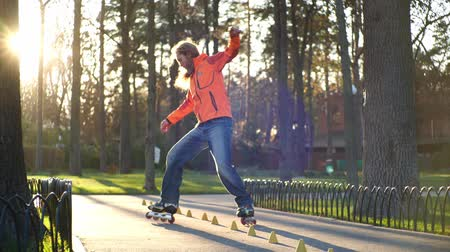 útil : A sports bearded guy on rollers makes various turns between training cones, accidentally overturning one of them. Professional training of a man in slow motion on roller skates in the autumn.