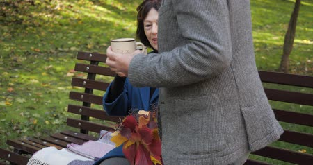 tutmak : Senior woman sits on a bench in the fall in the central park of the city. The husband brings his wife a cup of hot tea to keep warm in windy weather. Leisure in the fresh air in slow motion.