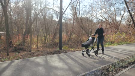 wozek dzieciecy : Young family walk with a sidecar on rollers in a morning city park in the fall. Dad does the tricks. Slow motion.