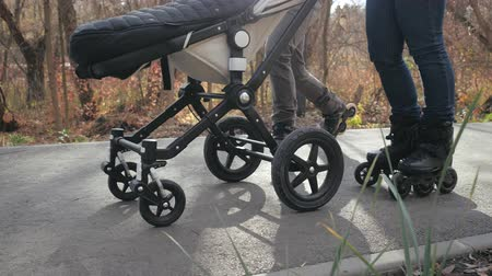 rolki : Young mom and dad are walking on roller skates with their baby in a stroller in autumn sunny weather. Down view Slow motion.