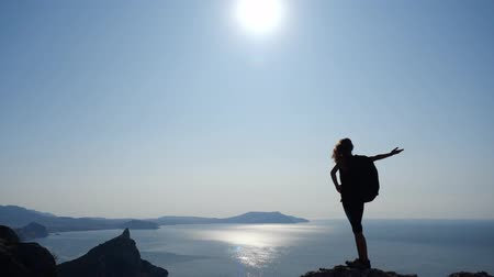 água salgada : The girl conquered a tall rock and admires the view of the sea and the salt in the clear sky. Athletic woman raises her hands and enjoys the beauty of nature under the rays of the sun in slow motion. Stock Footage