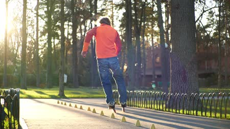 roller blading : Roller sport life. Active and athletic man performs professional roller skating technique in a cool city park. An experienced roller skates in the autumn in the fresh air in a park in slow motion. Stock Footage