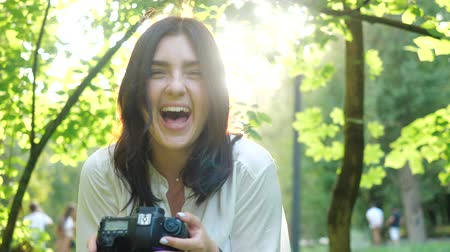 захват : Pretty young girl laughs loudly while browsing photos on professional photo camera. Pretty smiling and laughing girl photographer wearing white shirt takes photos in a park.