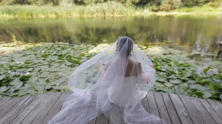 véu : The bride sits on a small bridge over the water and puts a veil on her head, back view. A girl sits and rests on a wooden pontoon near a beautiful colorful autumn forest mirrored in a mountain lake.