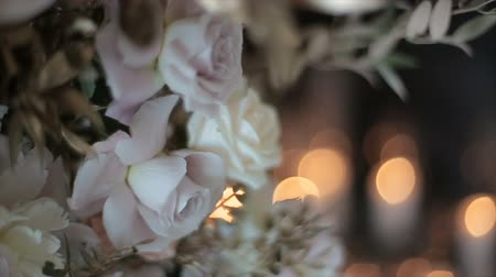 hortênsia : Snow-white roses stand in a vase against a background of blurry flickering glare of light and candles. Beautiful flowers for a wedding in the middle. The flickering of lights conveys a festive mood. Vídeos