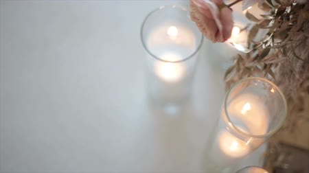 ortanca : Pink-and-white flower hangs over glasses with candles, a top view in a dipped form. Romantic gift for a girl on any occasion. Wedding of the newlyweds. Cozy and warm atmosphere in the building.