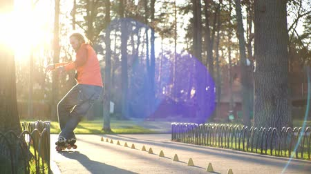 roller blading : Cool roller trains his roller skating technique, rides backwards and crosses legs and drives between cones. Down view training of an experienced bearded athlete in fine sunny weather in slow motion. Stock Footage
