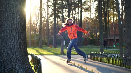 užitečný : Roller sport life. Active and athletic man performs professional roller skating technique in a cool city park. An experienced roller skates in the autumn in the fresh air in a park in slow motion. Dostupné videozáznamy
