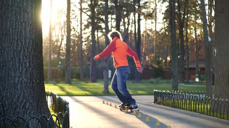 rolki : Man on rollers performs various turns and rides between training cones, crossing his legs. Professional roller skate training in a city park in autumn in sunny weather. Back shot in slow motion. Wideo