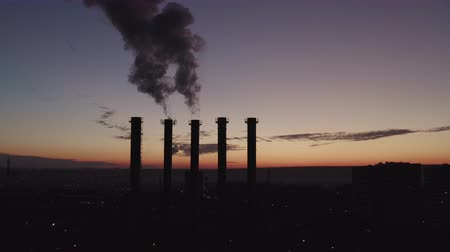 cooling tower : Silhouettes of five cooling towers against the backdrop of a big city and sunset. Beautiful sunset over a smoking thermal power plant. The camera moves over cooling towers and chimneys. Boiler room.