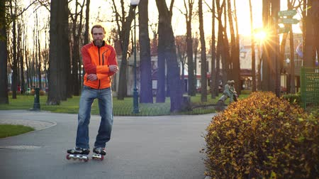 roller blading : Cool bearded man wearing orange coat and jeans dances on roller skates in autumn in a central city park on a background of trees. Active sports and healthy lifestyle. Side view in slow motion. Stock Footage