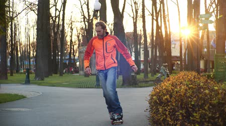 roller blading : Cool bearded man skates and dances on roller skates in autumn in a central city park on a background of trees. Active sports and healthy lifestyle. Side view in slow motion. Stock Footage