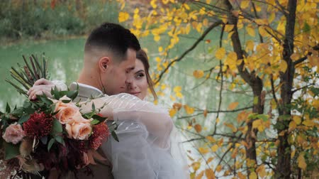 結婚した : Close-up portrait of Groom and bride hugging near a lake in autumn forest among Colored fall trees. Young attractive Happy loving newlyweds in a park in Slow motion.