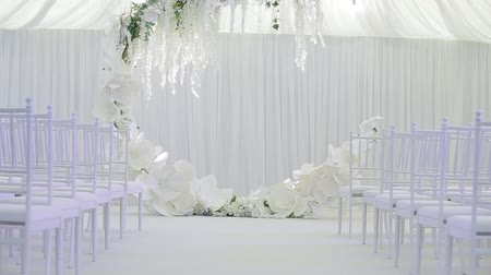 çelenk : Large spacious white wedding room with a large wedding cute wreath, under which the bride and groom become. White chairs for guests. Happy day for the newlyweds. Wedding party after the ceremony. Stok Video