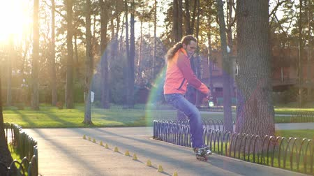rolki : Man on rollers performs various turns and rides between training cones, crossing his legs. Professional roller skate training in a city park in autumn in sunny weather. Close-up shots in slow motion.