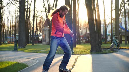 roller blading : A cool roller with a good stretch skillfully rides backwards between training cones. Comfortable training on roller skates in the fresh air under the sun in the central park of the city in slow motion.