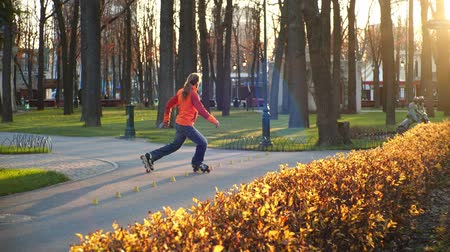 roller blading : Sports man roller skating professionally rides and trains on roller skates, performs various tricks and elements against the backdrop of a sunny autumn city park in slow motion. Useful lifestyle.
