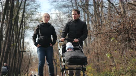 rolki : Happy family roller-skating, carrying a stroller with a baby, top-down shooting in slow motion. Cute couple man and woman walking on roller skates in the autumn city park in sunny weather among trees.