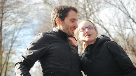 rolki : Cute couple man and woman hugging, wife leaned on her husband and bowed his head on his shoulder, front view close up. Happy parents are smiling, hugging and kissing in the citys cozy autumn park. Wideo