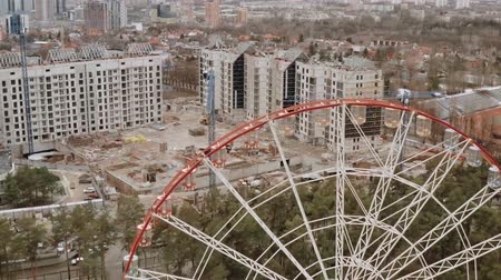 inacabado : Aerial shot from above of a construction site and houses under construction in front of the Ferris Wheel in Gorky Central Park in the city of Kharkov, Ukraine. Construction cranes on landscape.