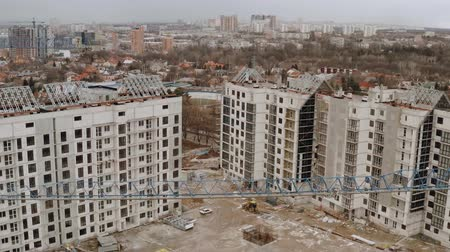 kusy : Top view of houses under construction. Aerial view of a construction site. An apartment or office building under construction. Tower cranes on a suburb landscape and blue sky copy space background. Dostupné videozáznamy