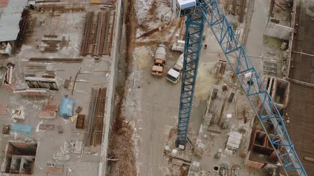 inacabado : High crane for construction from a birds eye view, as well as the construction site where a new multi-story building is being built. Top view of concrete mixer trucks and iron building materials.