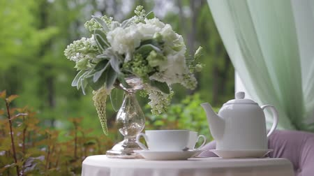 teacup : Hot tasty tea in white cups and a white teapot is served in the open air under a closed top on a white table decorated with a bouquet of white-green flowers. Beautiful scenery. Warm tea for warming. Stock Footage