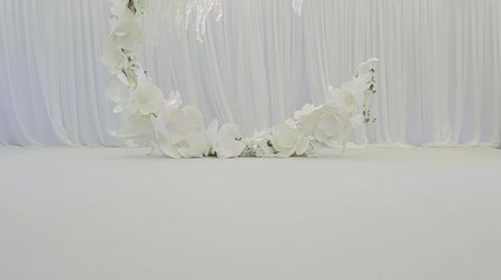просторный : Beautiful cozy large wreath for the wedding, under which the bride and groom become, and the wedding ceremony takes place. Large spacious white wedding room with white chairs for guests. Wedding party Стоковые видеозаписи