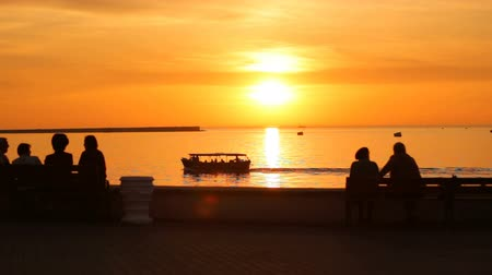 krím : Beautiful sunset over Black sea in the city of Sevastopol, Crimea. Silhouettes of people observing Amazing orange sunset over sea. Horizon of the sun with water. Vacation breaks.