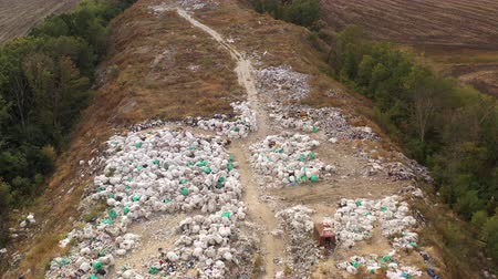 瓦礫 : Aerial shot of a large landfill in the city of Kharkov, Ukraine. Huge piles of garbage and bags of garbage and waste are lying on the ground for landfill. Top view of a contaminated surface in autumn.
