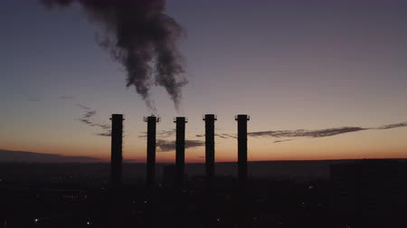kotel : Silhouettes of five cooling towers against the backdrop of a big city and sunset. Beautiful sunset over a smoking thermal power plant. The camera moves over cooling towers and chimneys. Boiler room.