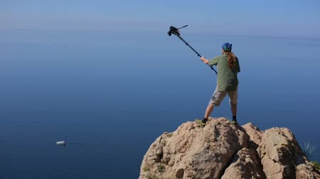 krym : An experienced operator shoots sea using monopod as a crane carefully standing on a high cliff in Crimea. Man with a professional camera takes pictures shoots video from a cliff edge on a hight.
