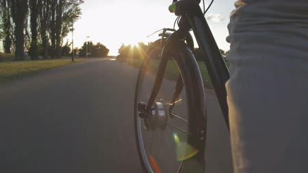 bisiklete binme : close-up of the front wheel of a bicycle and a man who cycling towards the sunset