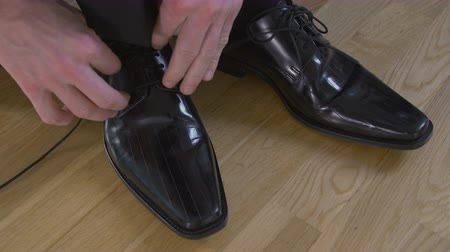 shiny : caucasian man with suit trousers that tie shoelaces on his black, shiny leather shoes