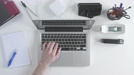 inventing : Top view of desk with office supplies. Man typing on his laptop. Drinking coffee and check off his to-do list. Stock Footage