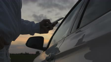 legal : Man sms texting using app on smart phone at sunset. Wearing a white jacket and standing beside a car
