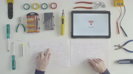 inventing : Top view software developer engineer looking at the circuit board drawing and is planning further development of its software. Tablet connection to wifi. Stock Footage