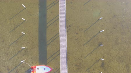 airial : Aerial view of a Wooden pier with attached boats a summer day Stock Footage