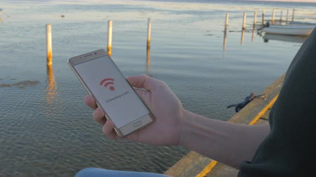 man sitting on a wooden pier holding a smart phone that connects to wifi