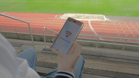 banda larga : man sitting alone in a stadium with a smart phone that connects to wifi