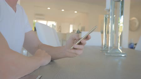 Man sitting in a chair at a table sms texting using app on a smartphone in a modern home