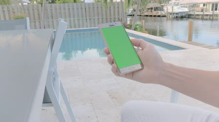 GREEN SCREEN man on vacation sitting by the pool holding his smartphone