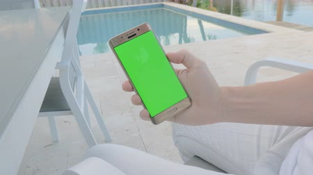 sharing : GREEN SCREEN man on vacation sitting by the pool holding his smartphone