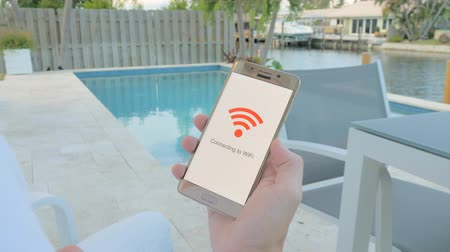 Man on vacation sitting by the pool holding a smartphone that connects to WiFi