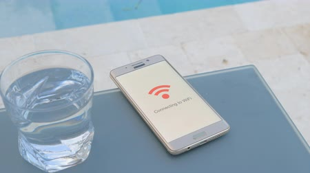 Smartphone on a table connects to WiFi beside the pool