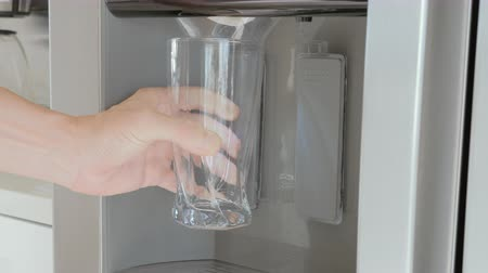 A man pours ice cubes from a fridge door into a glass
